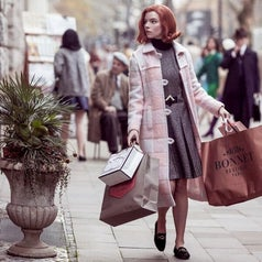 Beth holding multiple shopping bags; she is wearing a mid-length, marle grey dress with a pink and white coat on top