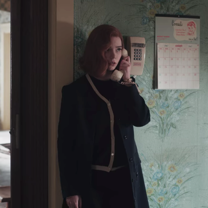 Beth leaning against a wall in her house while on the phone; she is wearing a dark blue coat, a navy blue cardigan with gold piping and a black top underneath, as well as dark-coloured pants