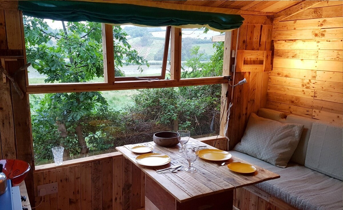 The inside of a wooden cabin, with a small dining table and large window looking out to farmland