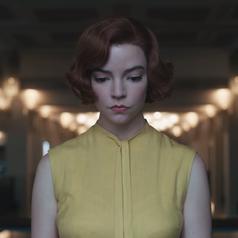 A closeup of Beth wearing a sleeveless mustard yellow blouse