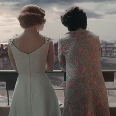 The back of Beth and her mother as they stand on their hotel room balcony and look at the view; Beth is wearing a fitted, sleeveless, white dress