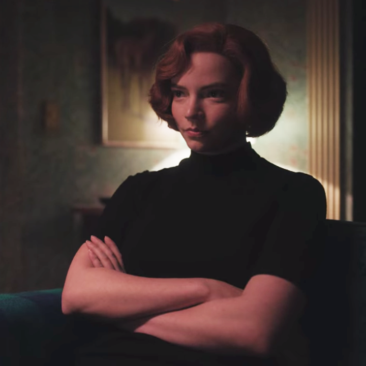 Beth smirking while sitting on a couch in her home; she has her arms crossed and is wearing a short-sleeved, black turtleneck