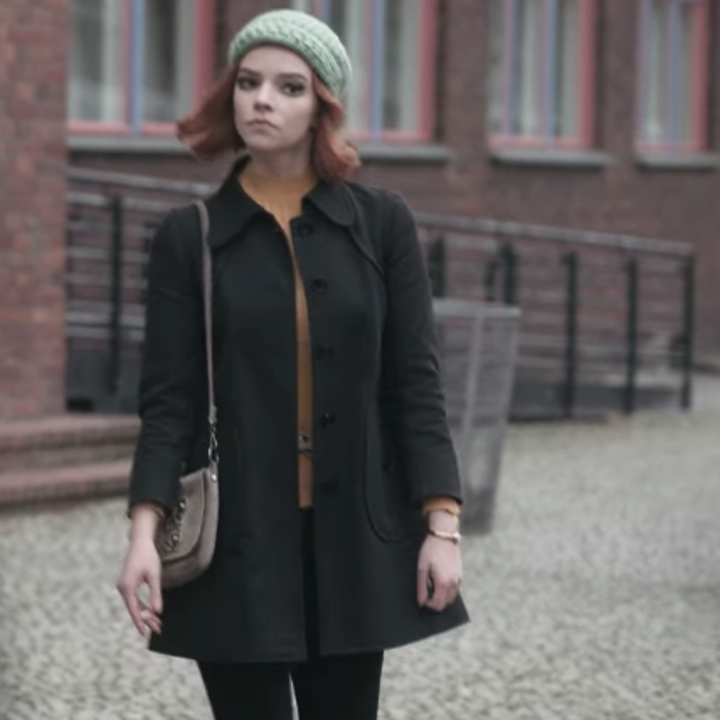 Beth standing outside; she is wearing a grey beanie with a mustard yellow turtleneck and a black coat