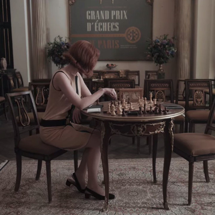 Beth sitting at an empty table with a game of chess laid out; she is wearing a sleeveless black and nude-coloured shift dress with black shoes