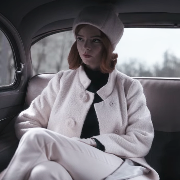 Beth in the backseat of a car; she is wearing a matching white beanie, coat and pants ensemble with a black turtleneck underneath