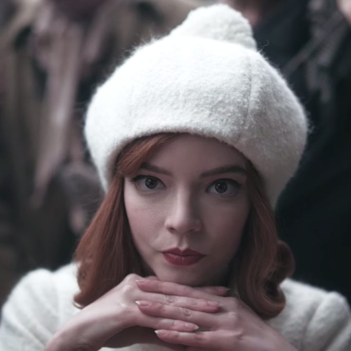 A closeup of Beth looking at the camera with her hands folded underneath her chin; she is wearing a white beanie and coat