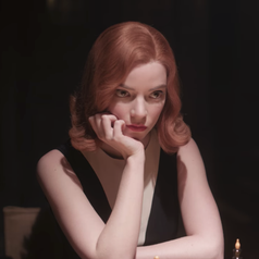 Beth with her face in her hand while playing a chess game in the Russian tournament; she is wearing a sleeveless black dress which has white, v-shaped colouring around the neckline