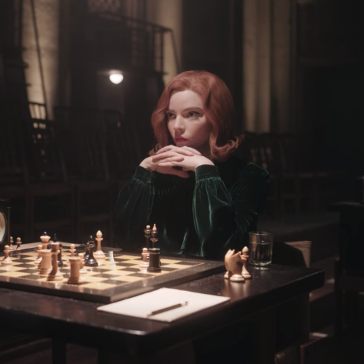 A closeup of Beth playing a chess game during the Russian tournament; she is wearing a dark green, velvet dress that has long sleeves