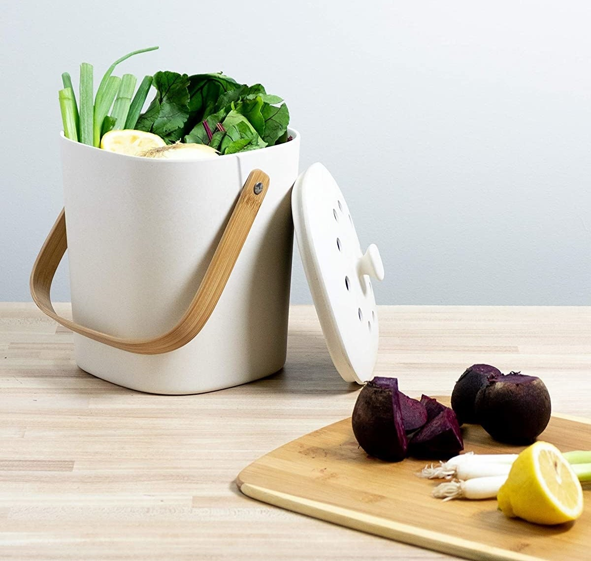 The white biodegradable composter which has a bamboo handle and vented lid