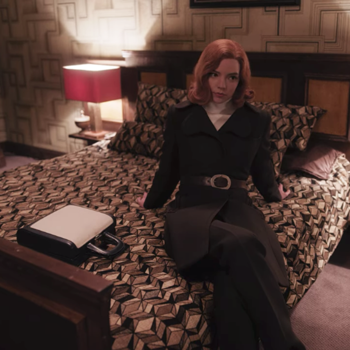 Beth leaning back on the bed in her hotel room; she is wearing a long, black coat that has been belted around her waist, a cream-coloured turtleneck and black pants