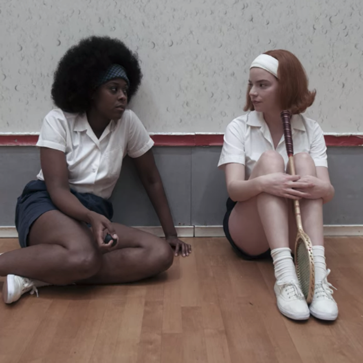 Beth sitting down on the floor of a squash court next to Jolene; Beth is wearing a thick, white headband to keep her hair off her face, along with a short-sleeved, collared white shirt, dark-coloured shorts and white sneakers and socks