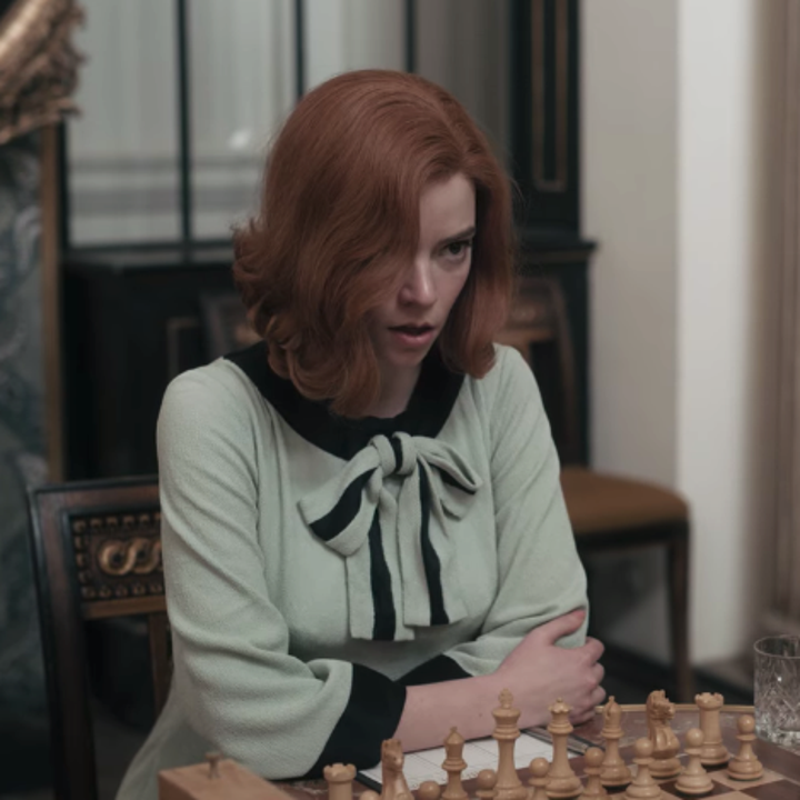 Beth wearing a pale blue, shift dress with a black Peter Pan collar; there is a bow just below the collar; she is playing a chess game against Burgov