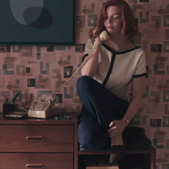 Beth sitting down on a table nook while on the phone; she is wearing a white shirt, which has black strip along the middle, the neckline and sleeves, and dark blue slacks and shoes