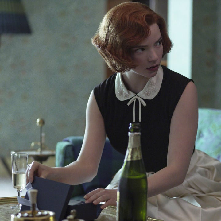 Beth sitting down on a couch; she is turned towards her mother, who is speaking. Beth is wearing a sleeveless black top with a white Peter Pan collar and a silky white skirt