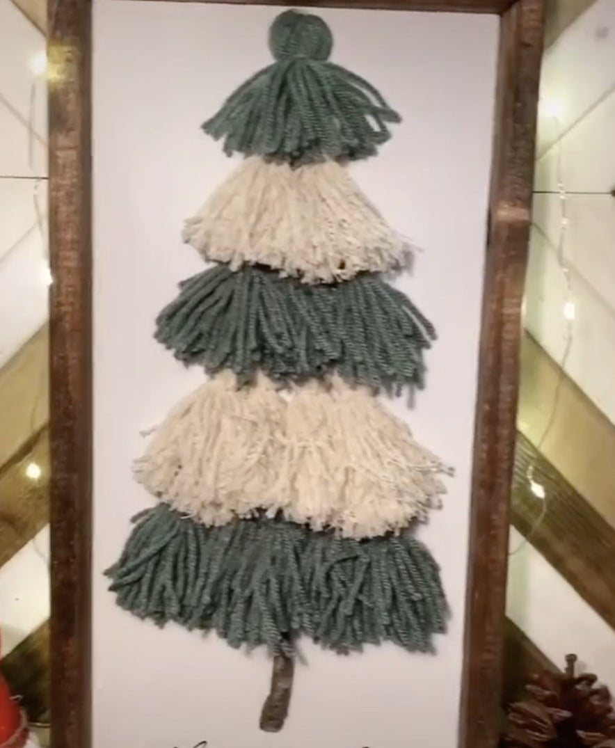 A green and white tree made from yarn in a frame