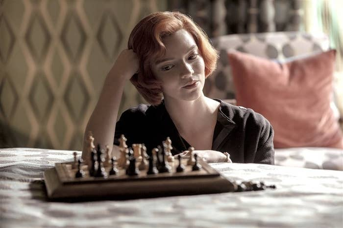 Beth sitting down and looking at a chess board that's on a bed in front of her