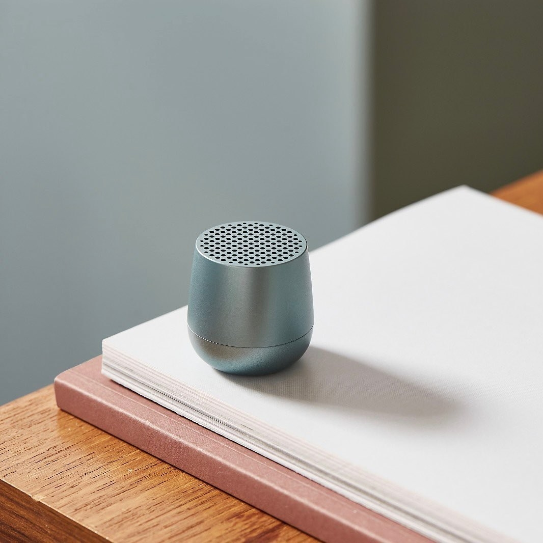 The tiny speaker on a stack of paper