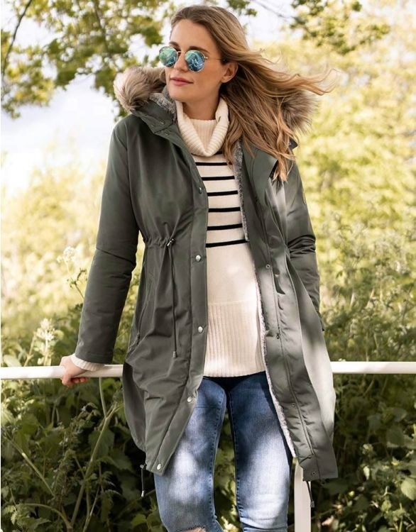 a pregnant woman wearing an olive green parka