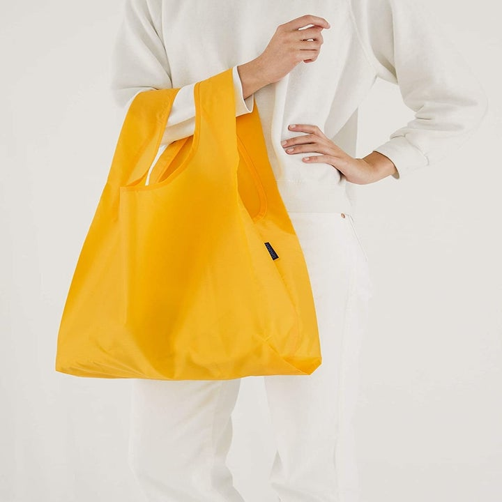 A model holding the tote in yellow