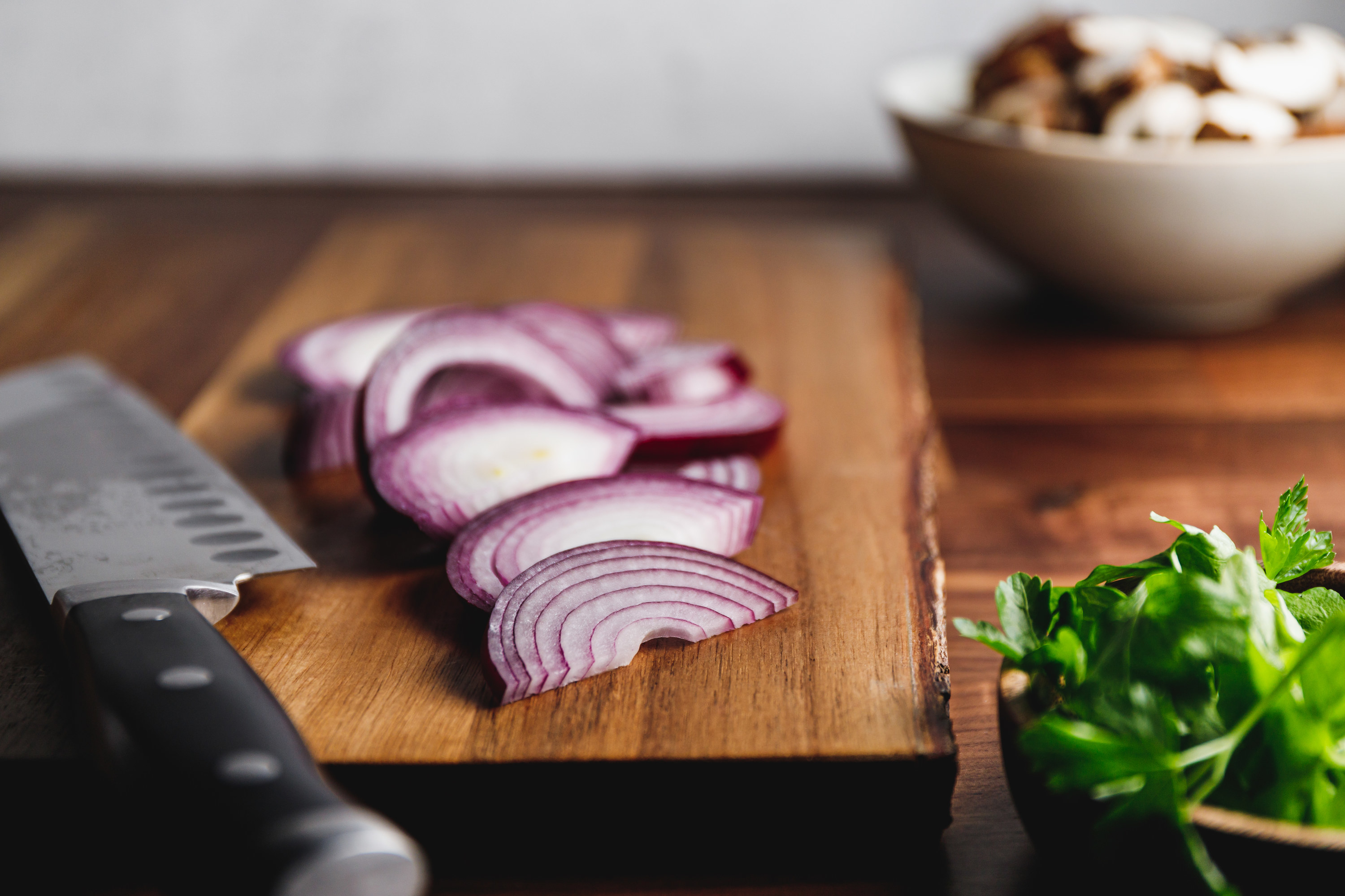 Purple onions chopped on a cutting board next to a knife, mint, and mushrooms