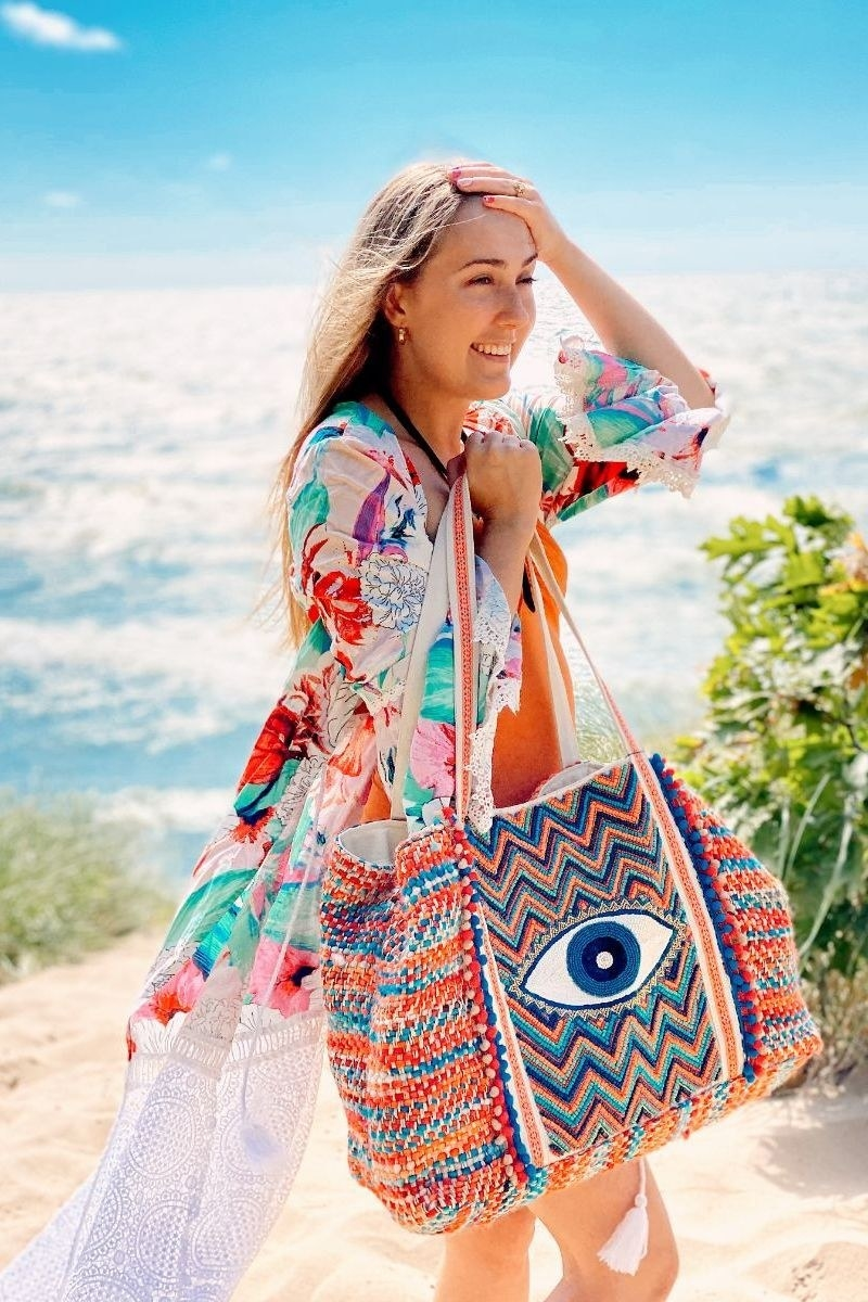 a model on the beach holding a colorful tote bag with a beaded evil eye design