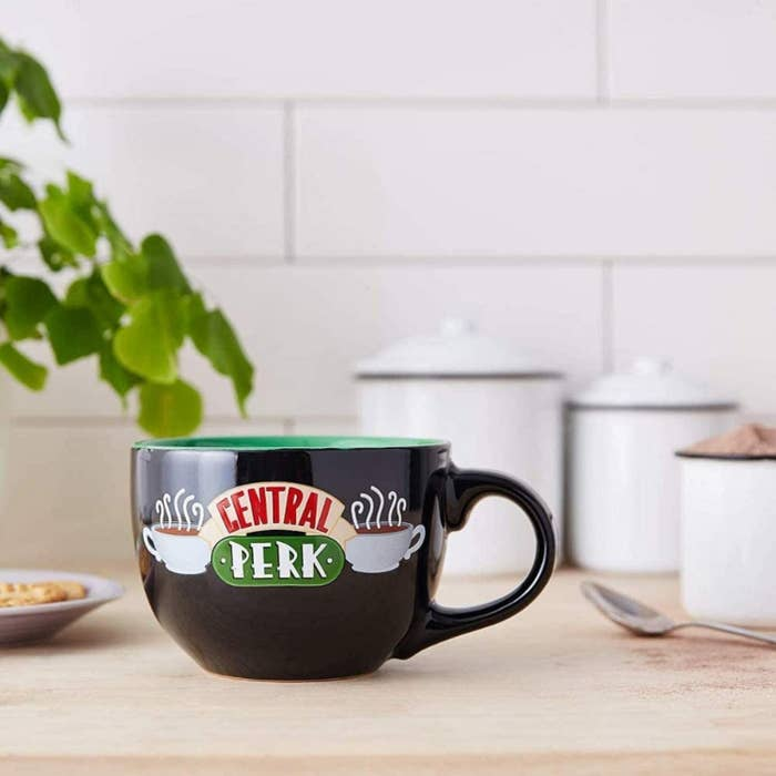 central perk mug on a kitchen table surrounded by jars and a spoon