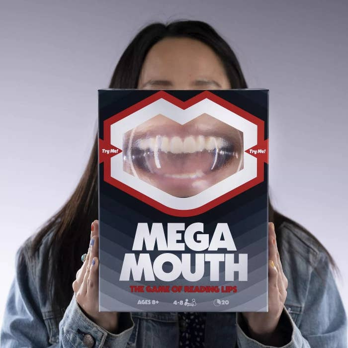 Model holds magnifier on game box up to their lips