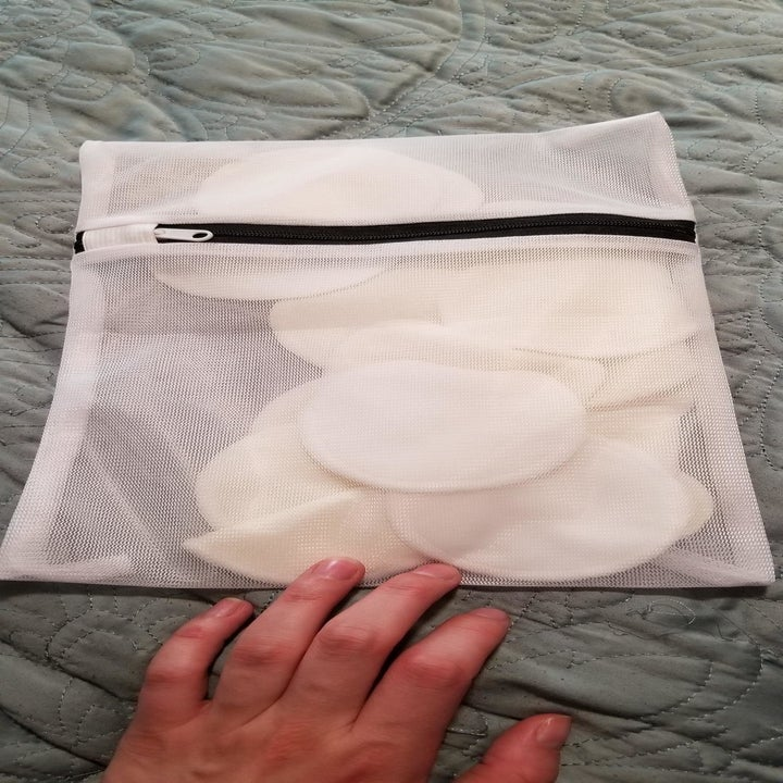 A reviewer holding the mesh bag of face pads