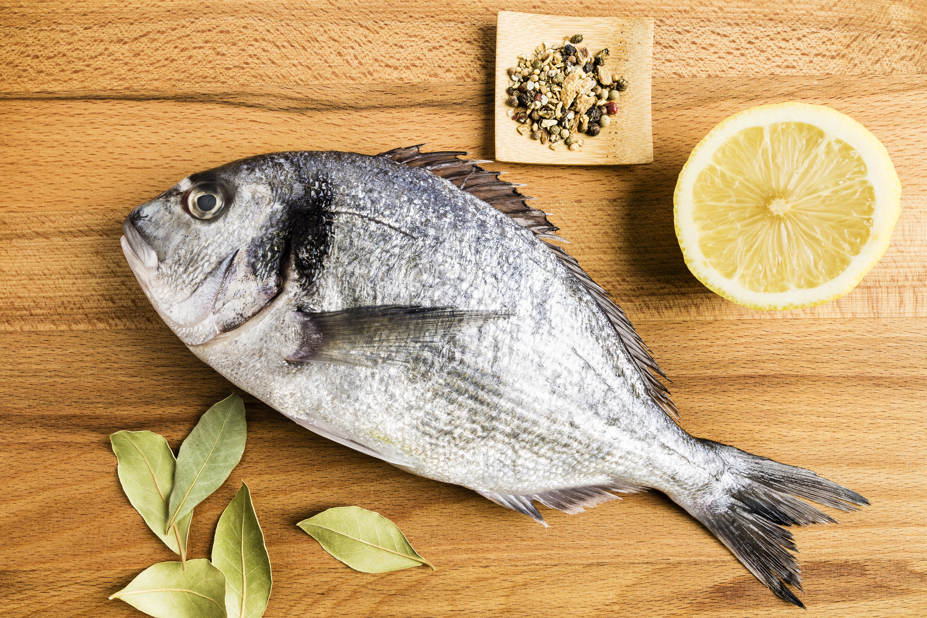 A cooked whole fish lays on its side next to a slice of lemon and some seasoning