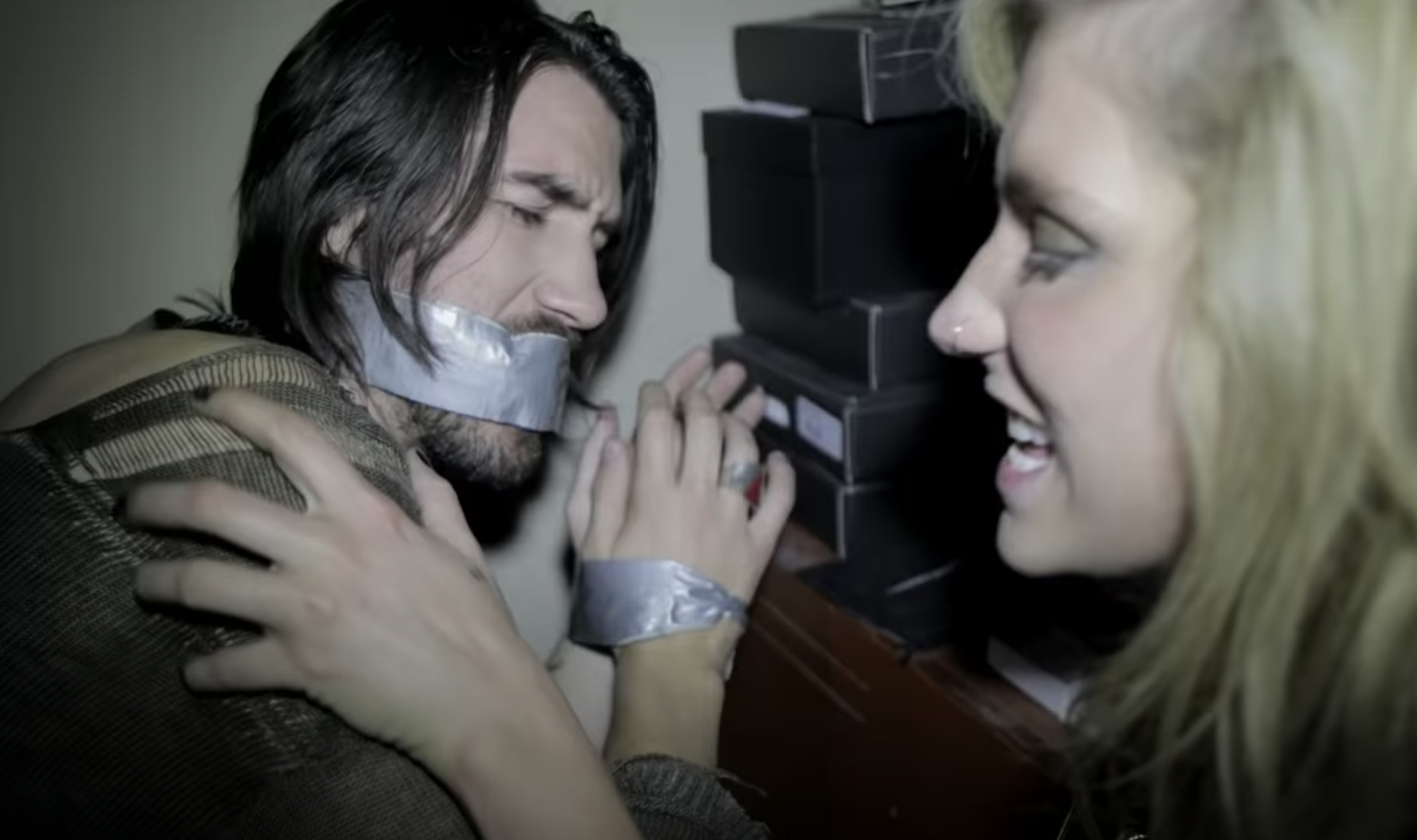 Kesha leans next to a man who is tied up and duct taped