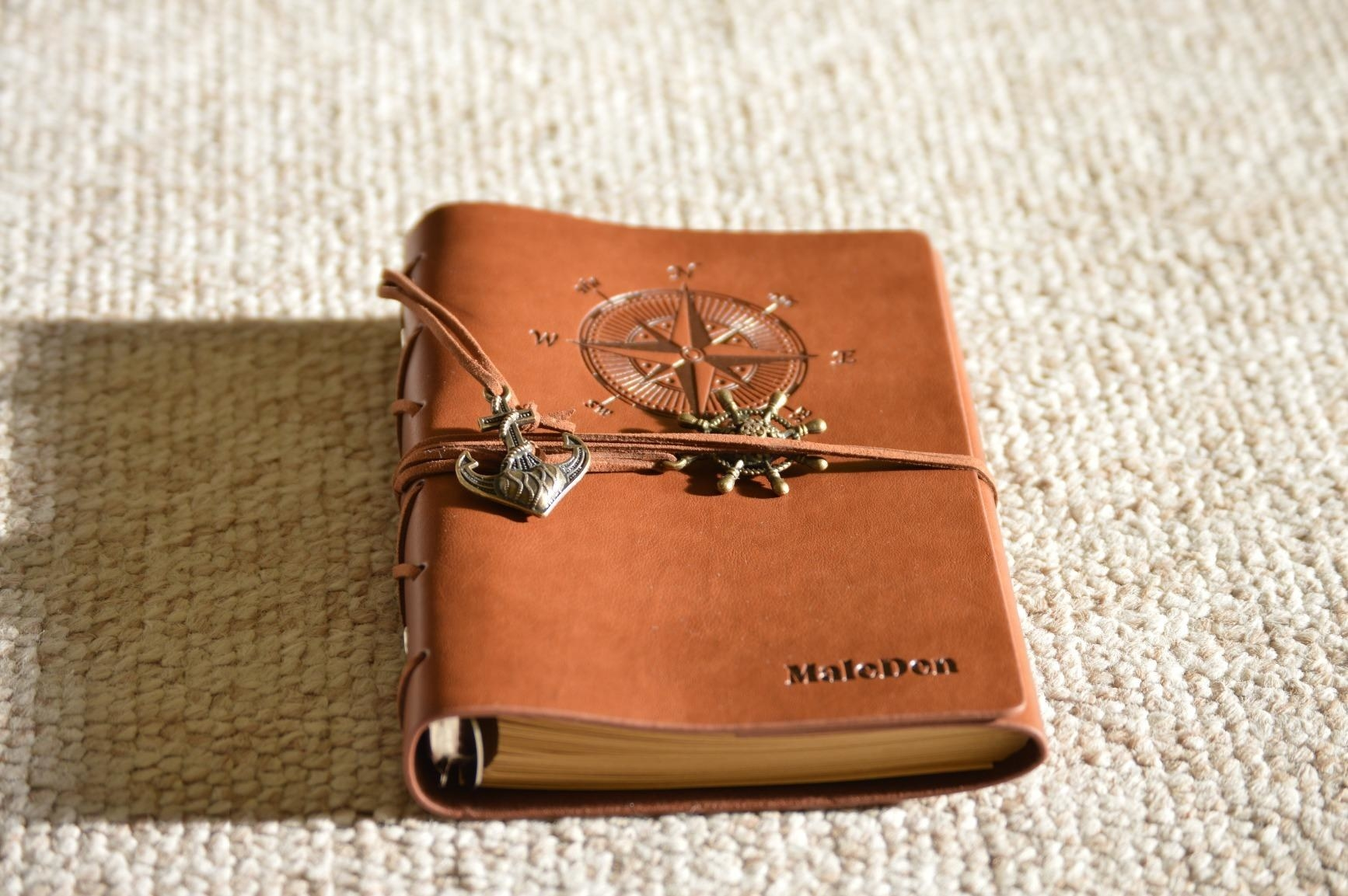 The journal with a brown leather cover engraved with a compass illustration and tie cords with charms around it