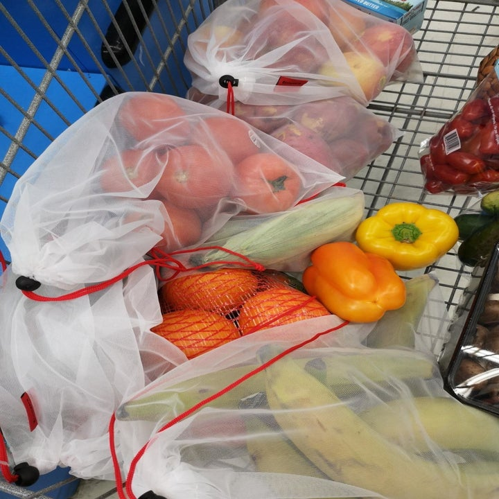 A reviewer's photo of them using the produce bags with tomatoes, bananas, and other produce