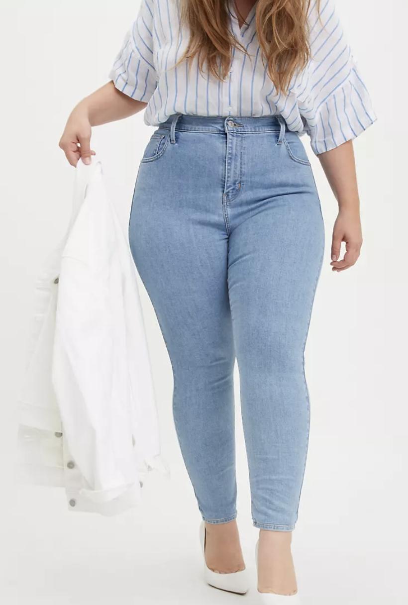 Model wears high rise skinny jeans in light wash
