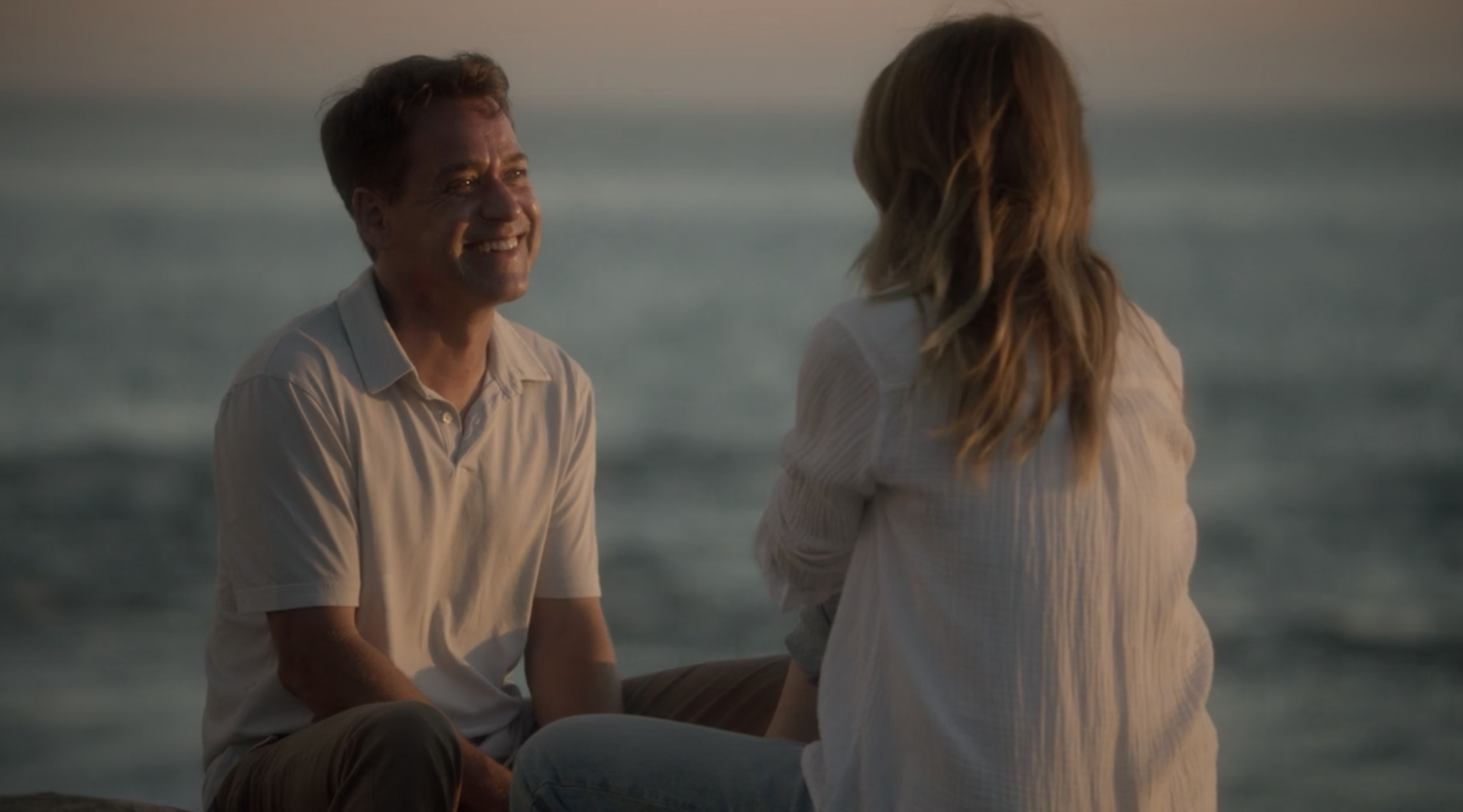 George smiling while talking to Meredith on the beach