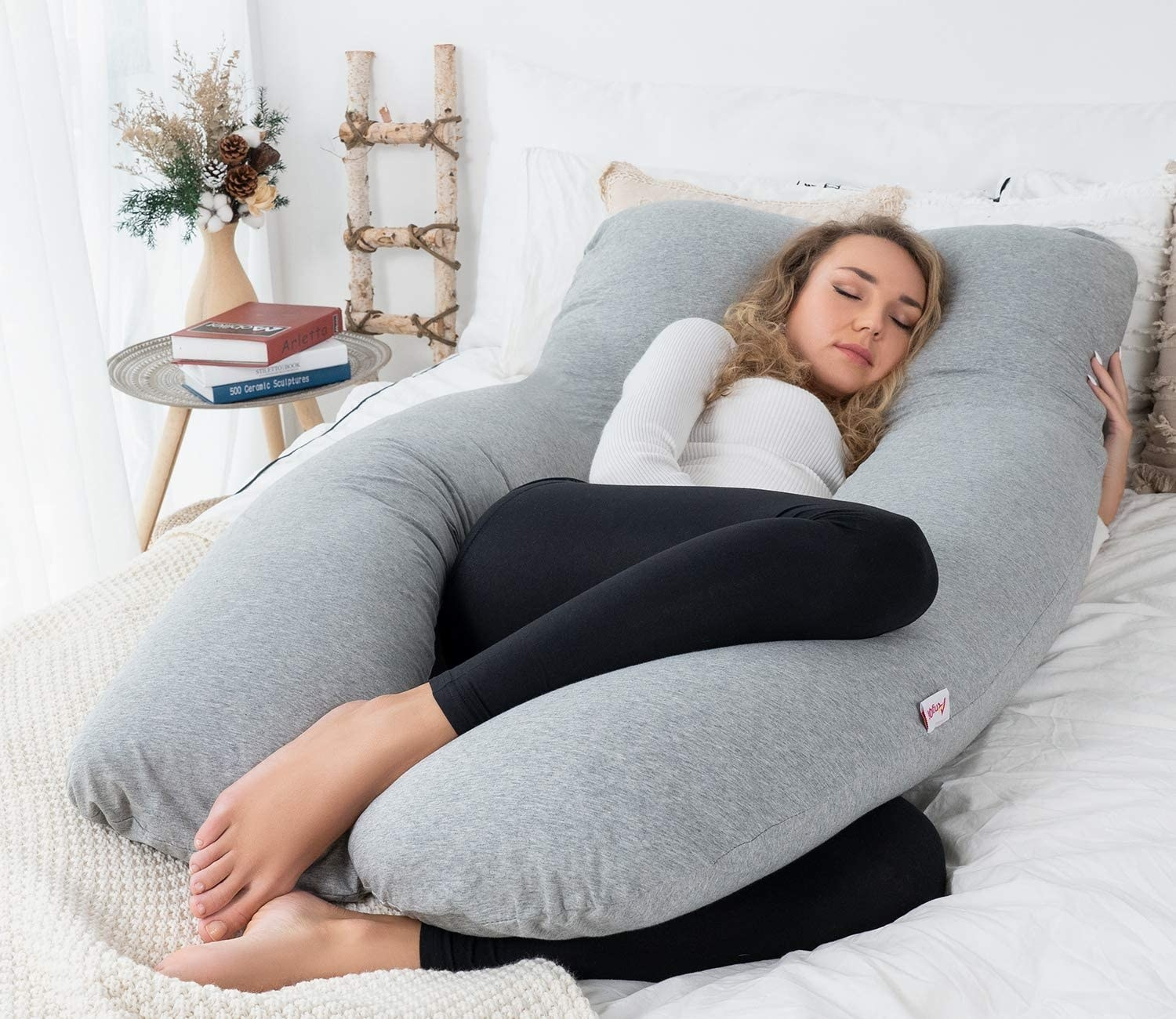 A person snoozing on the u-shaped body pillow
