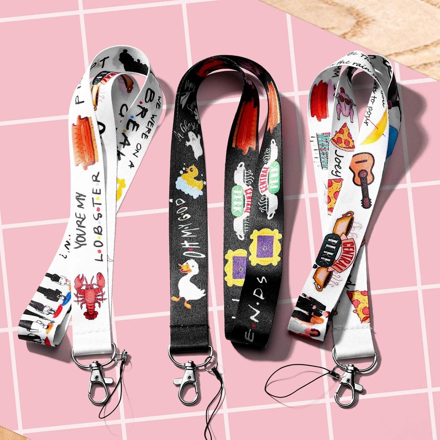 three lanyards with notable friends symbols like a lobster