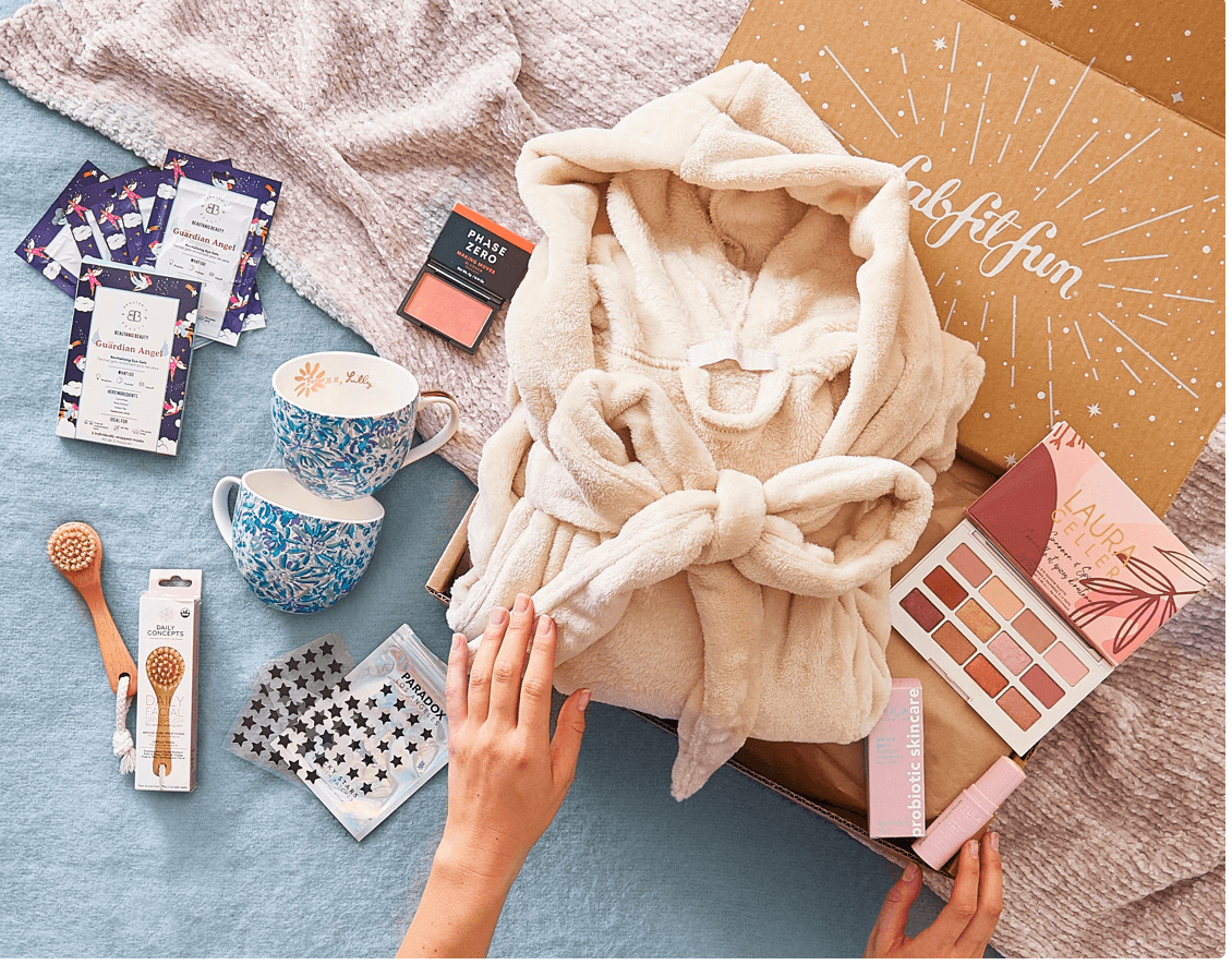 Hands opening a box with a robe, mugs, makeup, a scrub brush, and acne patches