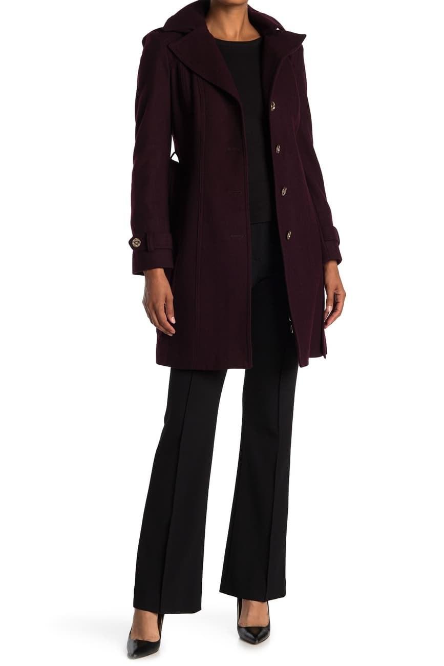 a model in a dark purple trench coat
