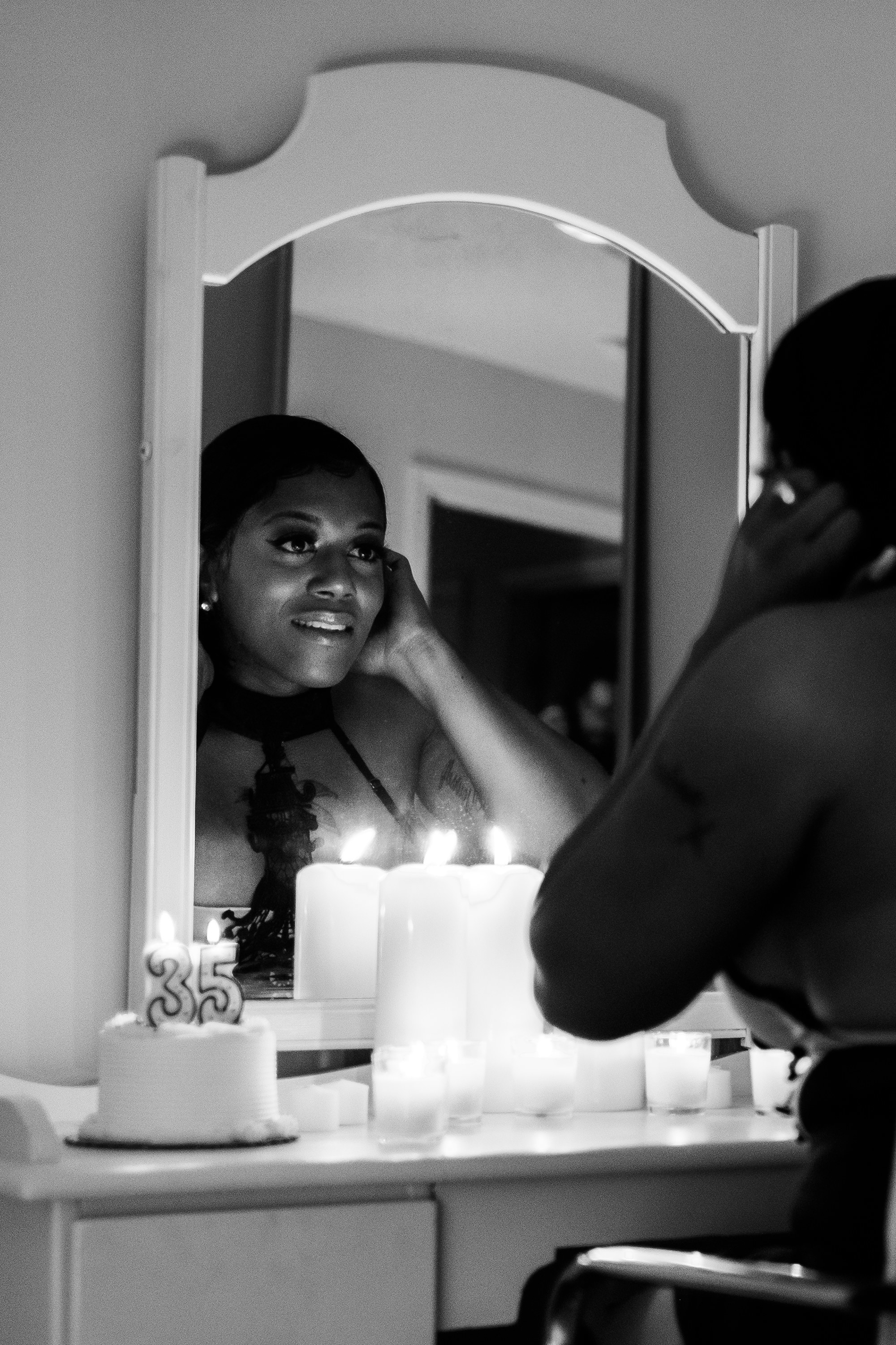 A black trans woman looks into the mirror and smiles candles are nearby