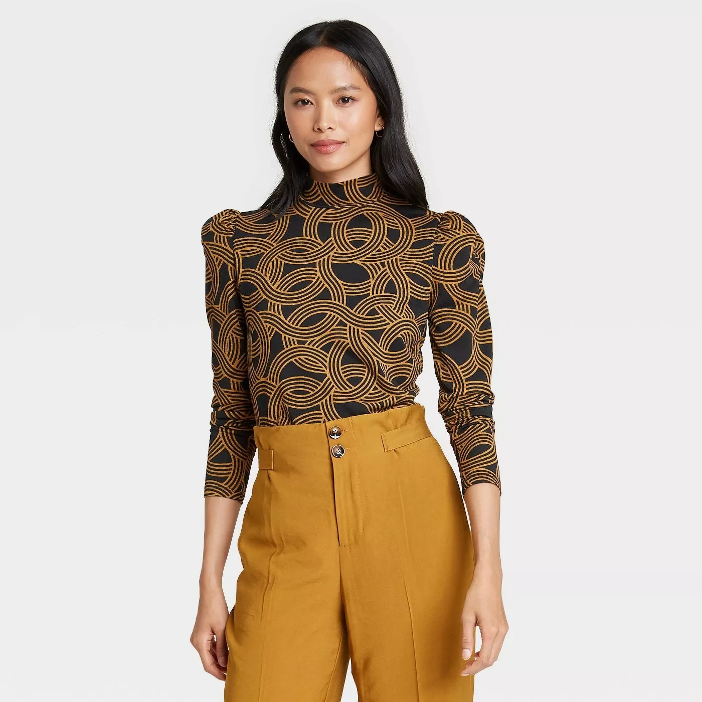 Black long sleeve top with circular gold pattern paired with high waisted mustard colored pants