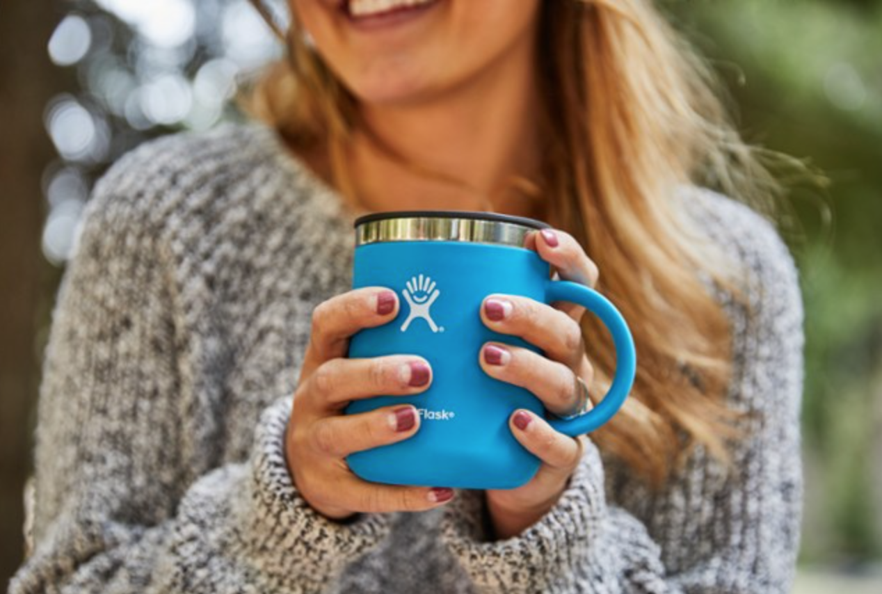 a model holding a blue mug