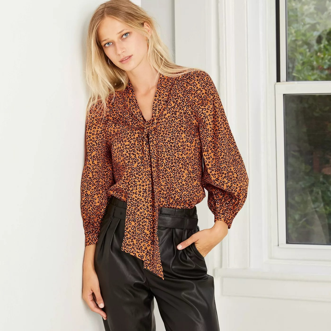 A brown and black leopard blouse with extra fabric hanging
