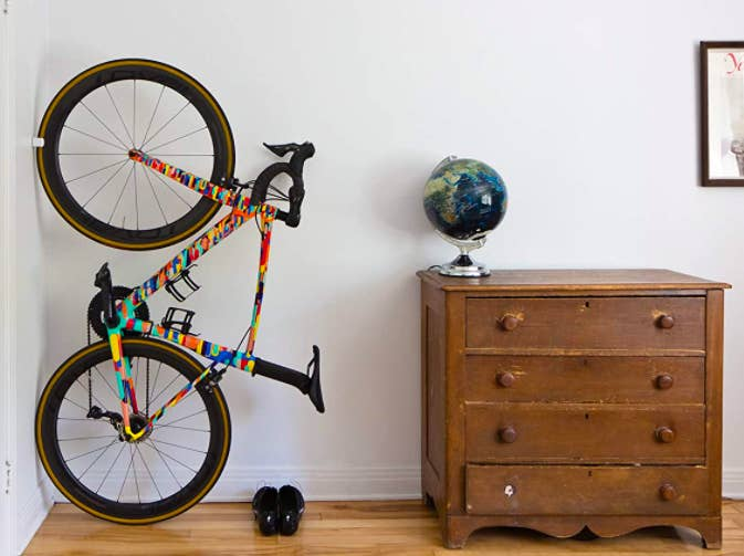 A bike stored vertically with a clip that attaches to the front wheel