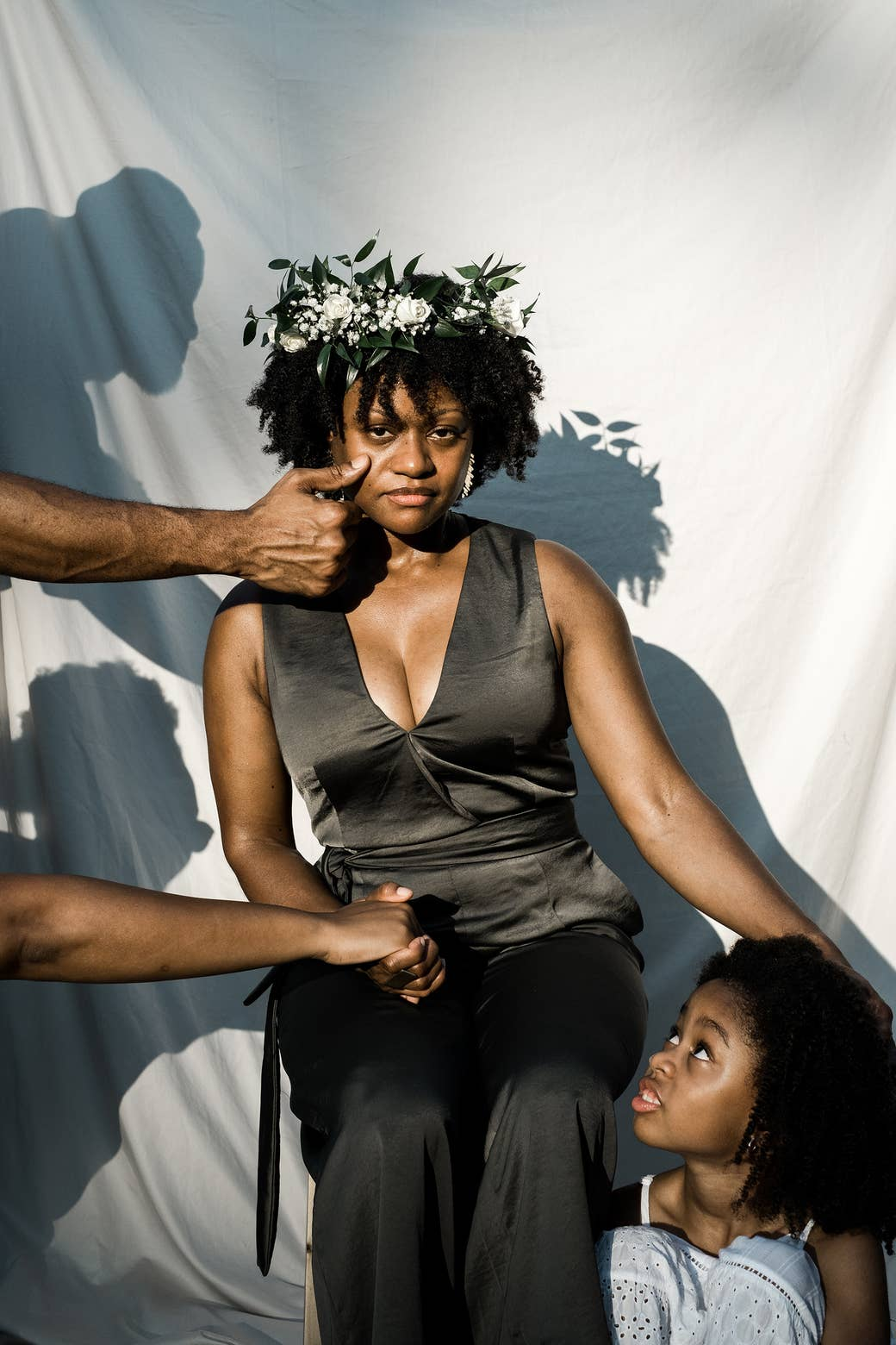 A Black woman in a flower crown with a young girl by her right side and two male hands reaching out to her from the left.