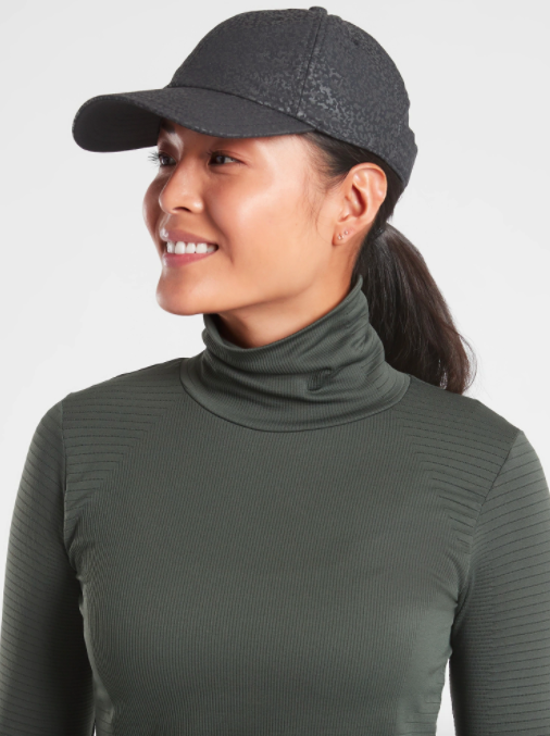 Model wears black reflective Athleta baseball cap with gray mockneck top