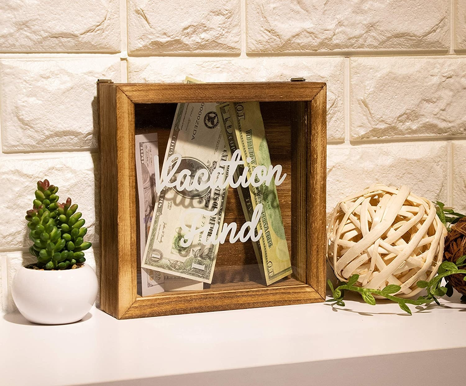 "A wooden shadow box that says ""Vacation Fund"" and has money inside"