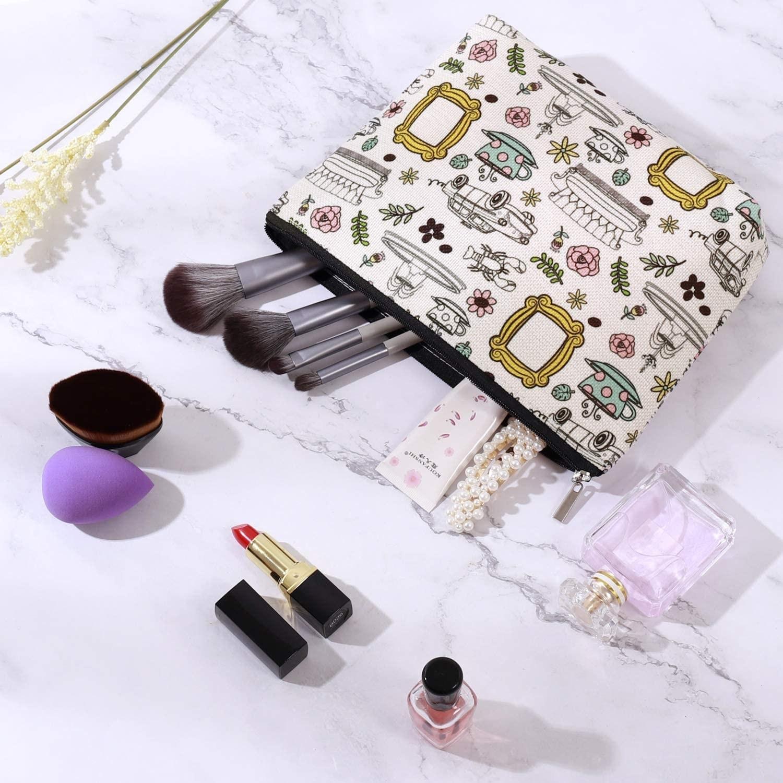 makeup bag with brushed, perfumes, nail polish, and beauty blender