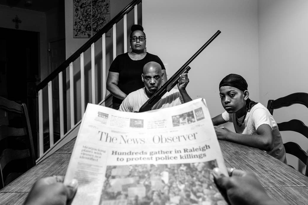 A newspaper in the foreground with a headline about police killings, with a Black family at their table in the background. The man is holding a rifle.