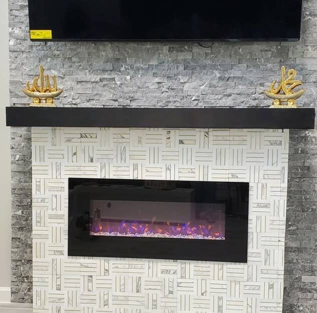 Reviewer's picture of the electric fireplace attached to their wall