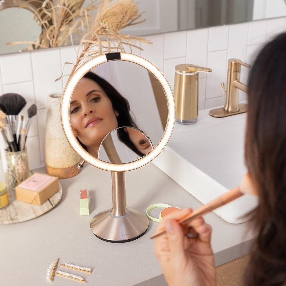 Model using the LED mirror to apply makeup